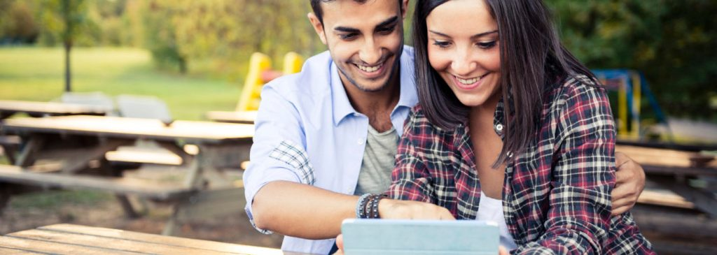 Young multi ehtnic couple in love using a digital tablet at the park.