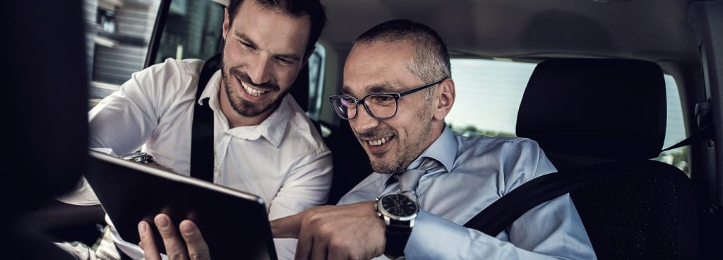 Smiling business colleagues using touchpad on the backs eat of the car. Focus is on businessman with glasses.